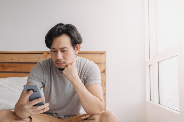 Man looking at smartphone with serious face