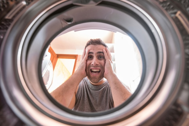Man looking at stained bleached cloth in washing machine