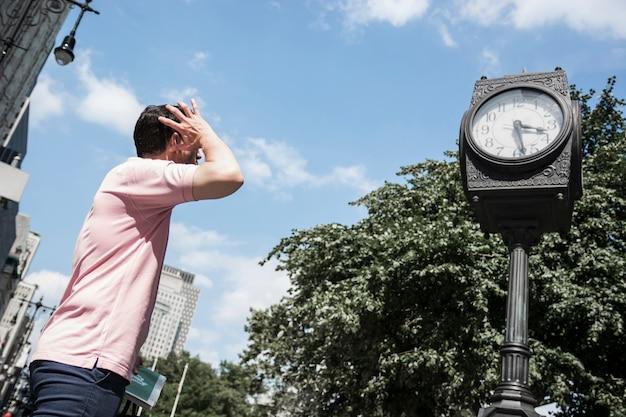 Man looking at street clock