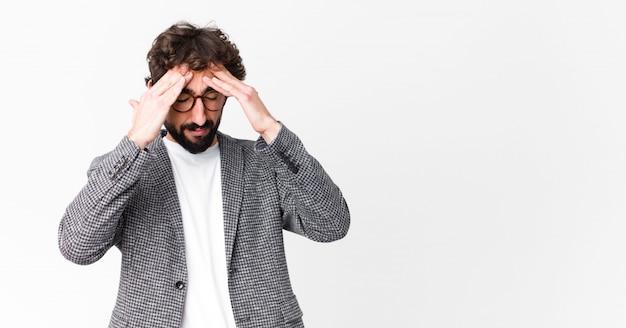 Человек выглядит напряженным и разочарованным, работает под давлением с головной болью и обеспокоен проблемами