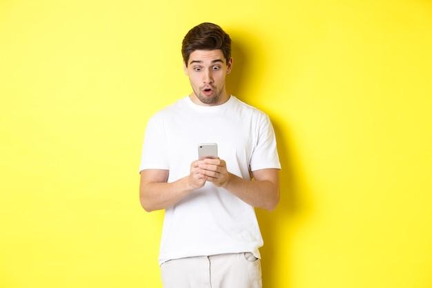 Человек выглядит удивленным в смартфоне, читая сообщение по мобильному телефону, стоит в белом костюме против