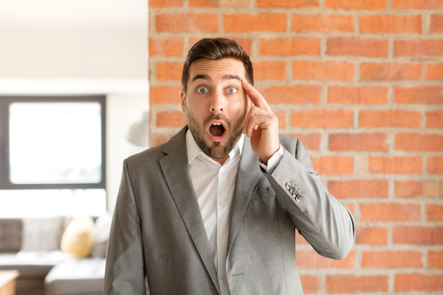 Man looking surprised, open-mouthed, shocked, realizing a new thought, idea or concept
