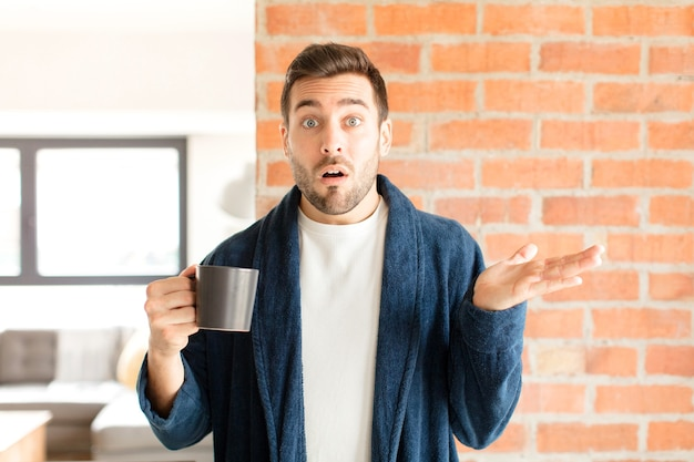 Man looking surprised and shocked, with jaw dropped holding an object with an open hand on the side