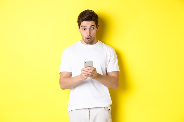 Man looking surprised in smartphone, reading message on cell phone, standing in white outfit against
