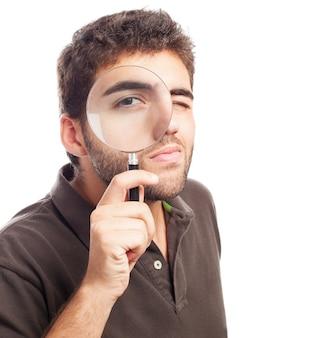 男は、虫眼鏡を通して見ます