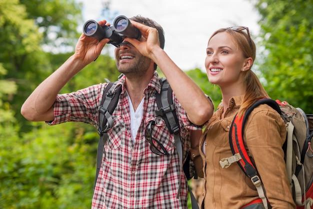 Man looking through the binoculars. hiking time