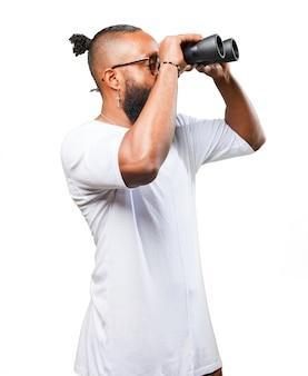 Man looking through binoculars to the side