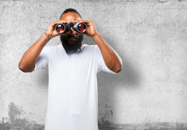Man looking through binoculars with gray background