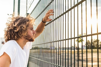 Man looking through fence