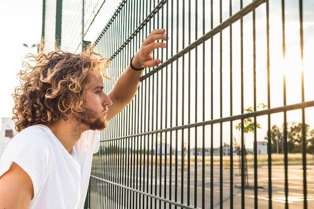 Человек смотрит через забор