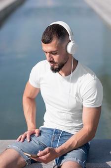 音楽を聴きながら携帯電話を通して見ている男