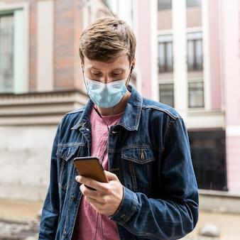 Uomo che guarda attraverso il suo telefono mentre indossa una maschera medica