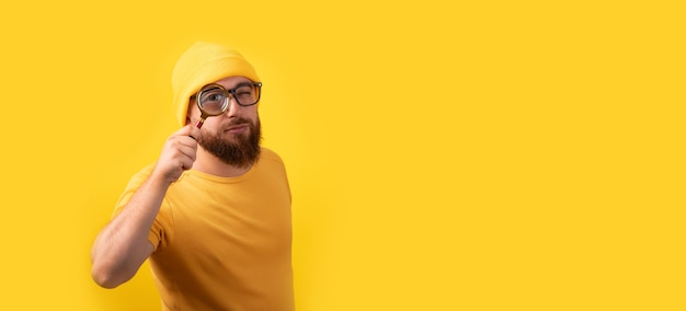 Man looking through magnifying glass over yellow background, searching concept, panoramic image