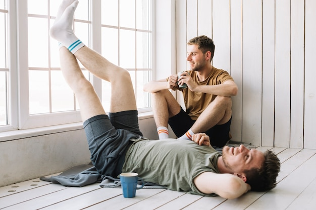 Man looking through window while his friend lying on floor