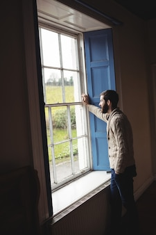 Man looking through window
