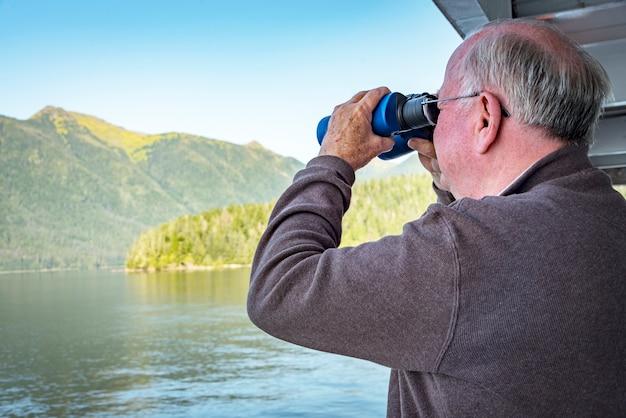 A man looking thru a binoculars on a cruise ship in alaska