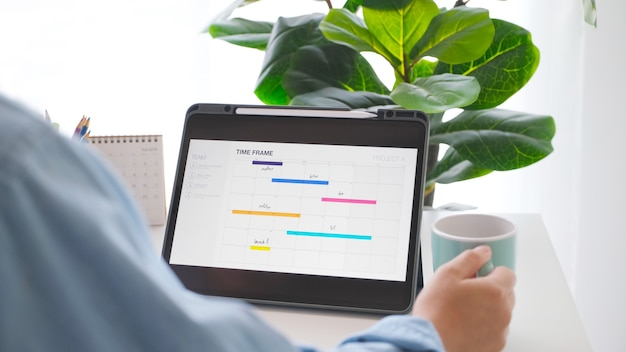 Man looking at time frame planner on digital tablet screen