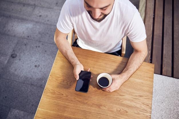 스마트 폰을 찾고 위에서 커피 야외보기를 들고 남자