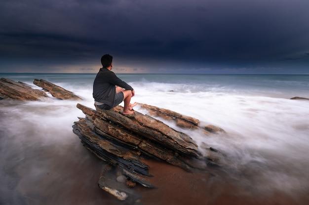 海がバスク国ビダールの岩にぶつかる間、海を見ている男。