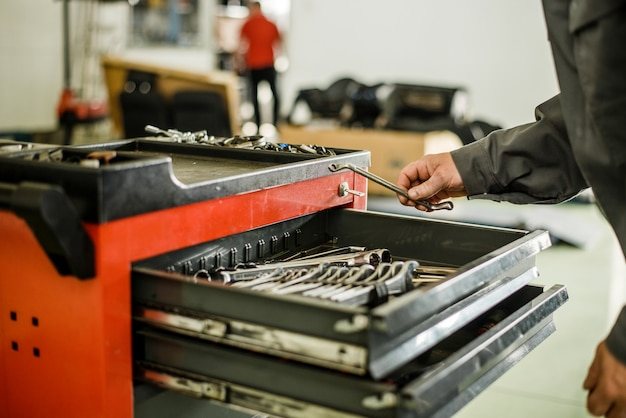 Man looking for tools in toolbox.