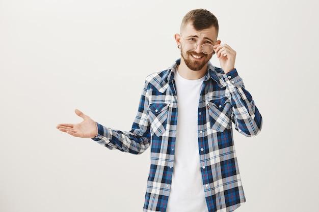 Un uomo dall'aria indifferente, che si fa beffe di cose stupide, si mette gli occhiali
