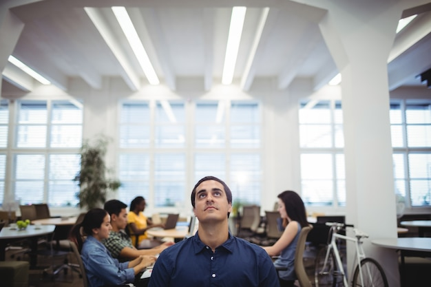 Man looking up while colleagues working in background