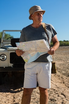Man looking way while holding map on field