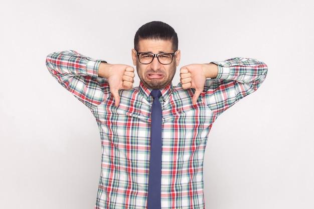 Человек смотрит с большими пальцами руки вверх и не любит жест