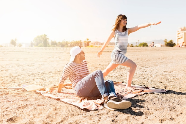 Man looking at young woman exercising on beach