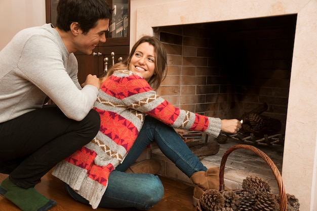 Man looking at young woman ignite big match in the fireplace