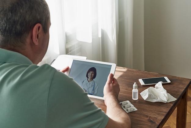 男はタブレット、医師へのビデオ通話、医師とのオンライン通信を見ます。遠隔医療
