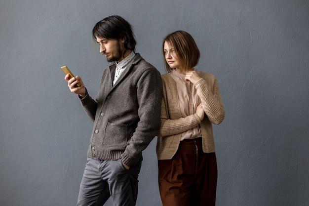 Мужчина смотрит на телефон, а женщина выглядывает сзади