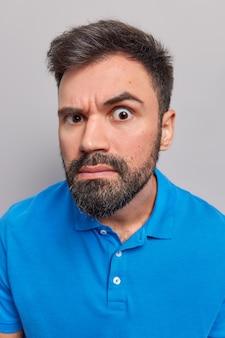 Человек внимательно смотрит в камеру, скрупулезное выражение лица, носит повседневную синюю футболку, позирует на сером