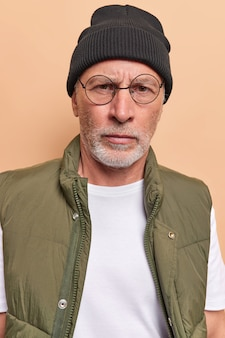Man looks directly at camera wears round spectacles hat and vest listens attentively information isolated on beige