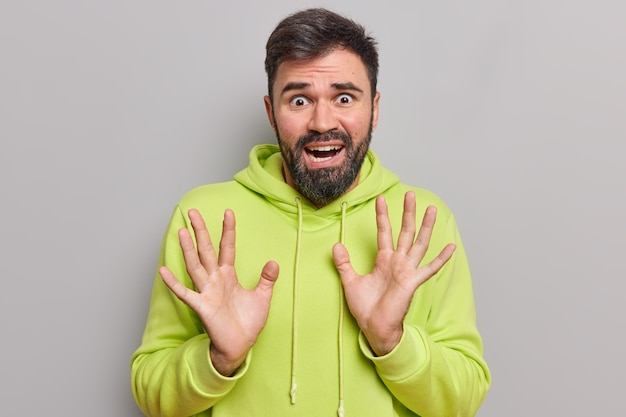 Man looks frightened has phobias raises palm tries to protect himself from something awful wears casual hoodie looks desperate and devastated isolated on grey