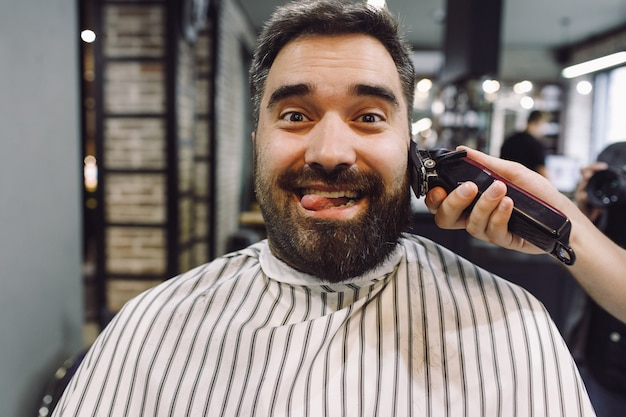 Man looks funny while barber works on him in the barber-shop