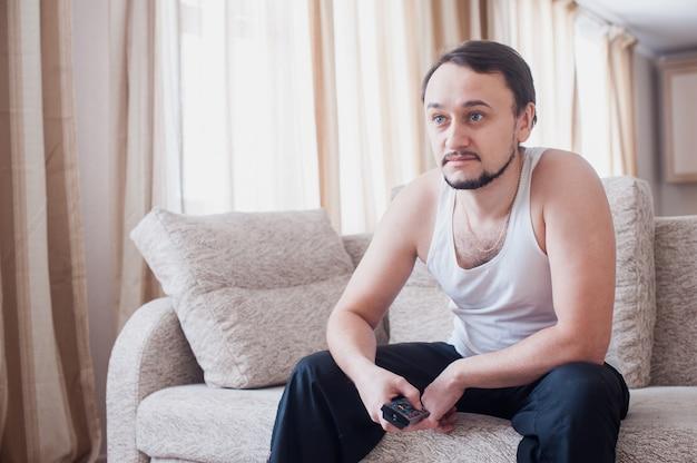 Человек смотрит интересную передачу по телевизору