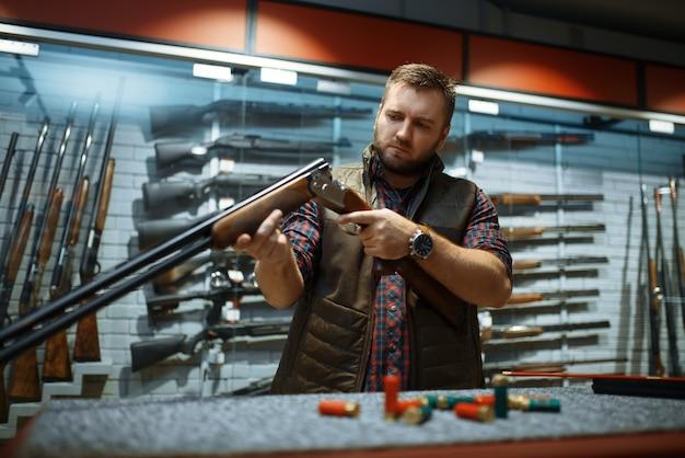 Мужчина смотрит на ствол винтовки у прилавка в оружейном магазине