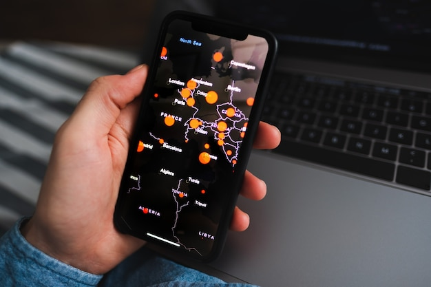 Man looks online map of the distribution of coronavirus in the usa on a smartphone