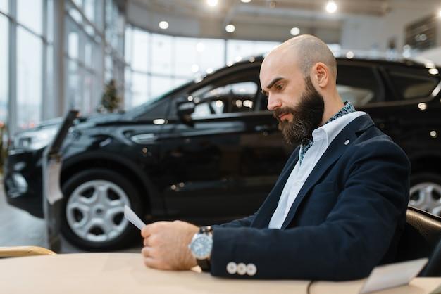 男は自動車販売店で新車の価格を調べます。