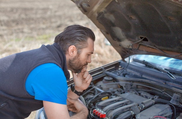 A man looks thoughtfully at the engine under the hood during a breakdown on a rural road.