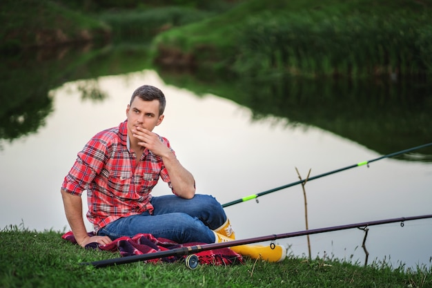 A man looks thoughtfully into the distance during a fishing trip