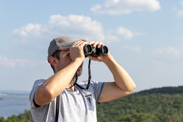 A man looks through binoculars against a scenic view of a wide river on a hill on a sunny day