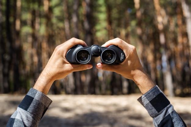 男は森の向こう側に双眼鏡を通して見ます。
