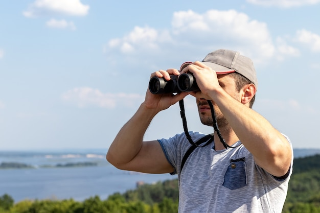 A man looks through binoculars at a scenic view of a wide river on a hill on a sunny day