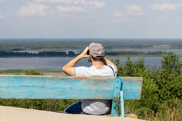 A man looks through binoculars at a scenic view of a wide river while sitting on an old wooden bench on a hill. back view