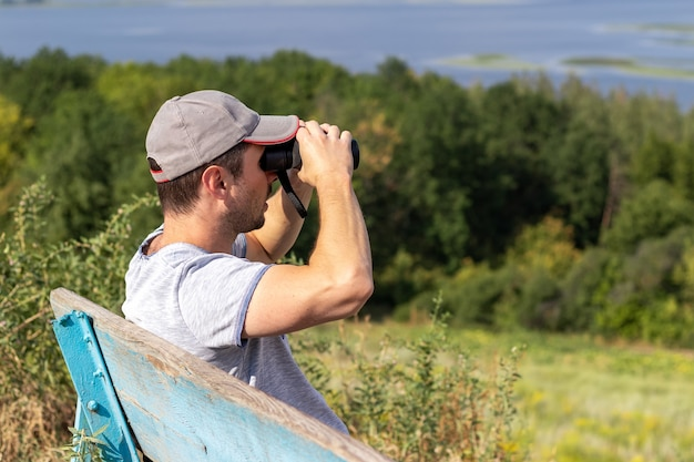 A man looks through binoculars at a scenic view of a wide river while sitting on an old wooden bench on a hill. side view