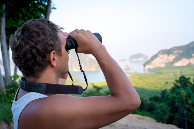 A man looks through binoculars on the sea rocks