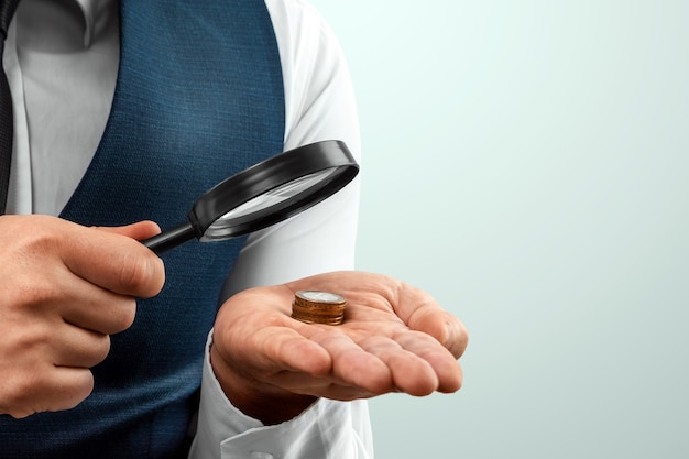 Premium Photo | A man looks through a magnifying glass at a stack of coins  in his palm. small salary, bankruptcy.