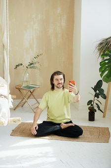 Man in lotus pose holding phone, handsome guy with long hair practicing yoga at home online with red telephone